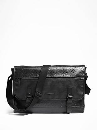 Safely store your laptop, documents and whatever else you need in this very-now faux-leather messenger bag. An embossed skull pattern adds a subtle but stylish accent, making it the ideal accessory for both your personal and professional looks.      • Black faux-leather exterior. Matte black hardware. • Embossed micro-skull and triangle pattern. Dual buckle detail on front with skull stud embellishment. Embossed logo patch. Fold over flap with snap button closure. • Exterior front zipper pocket and back slip pocket. Interior features zipper pocket, cell phone pocket, an additional multi