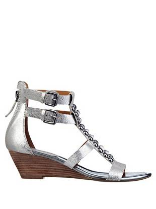 """It's our new wear-everywhere pair: with a wearably low wedge (that has just enough height) plus glimmering studded trim, these metallic sandals are a style powerhouse.  •Open-toe wedge sandals. Stud and rhinestone embellishment at vamp. Buckle detail at outer ankle. •Zipper closure at heel •Stacked wedge •2"""" heel •Material: Leather"""
