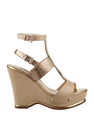 Make your warm-weather debut in these undeniably sexy wedge sandals. Leather straps and metallic accents bring effortless elegance to this essential pair.