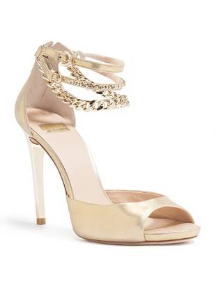 """This sandal is the ultimate in sexy feminine style for evening.  Dripping in lust-worthy chains, it adds the ultimate compliment to any night-out look.  •Open toe high-heel sandal. Gold-tone hardware.  •Black: Black leather with gold metal heel  •Gold: Gold textured leather with gold metal heel  •Multi: White toe strap, navy blue ankle strap, shiny red heel •Dual buckled ankle strap with chain strap and accent •Zipper closure  •4 ¼"""" heel"""