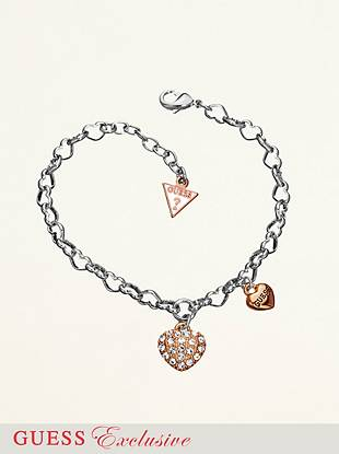 "A classic charm bracelet is made flirty and sweet. Amp up the glam factor and wear it with rhinestone embellished hoops for an eye-catching, late-night look. • Crystal covered heart and engraved logo charm dangle from silver-tone heart chains. • 7"" length • 1 ½"" extender • Lobster clasp • Nickel and lead free • Includes exclusive drawstring jewelry pouch."
