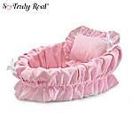 "It's naptime for your baby doll and what better way to rock her off to dreamland than in this beautiful wicker bassinet with a comfy pink liner and matching pillow. This So Truly Real® baby doll accessory is custom-designed to fit all of our collectible 10"" dolls. Just imagine how much your little one will love her new bed, accessorized with lovely pink details!Don't wait to tuck your little sleeping baby into this pretty bassinet and watch her drift off to sleep. This white wicker basket bassinet is fully lined in signature So Truly Real pink-and-white gingham fabric with a padded bottom for support. A matching pillow edged in lace is also included for your doll to rest her little head. This is perfect accessory for your collectible So Truly Real baby doll or to give as a special gift for a doll collector. Heavy demand is expected, and you won't want to miss out. Order now!"