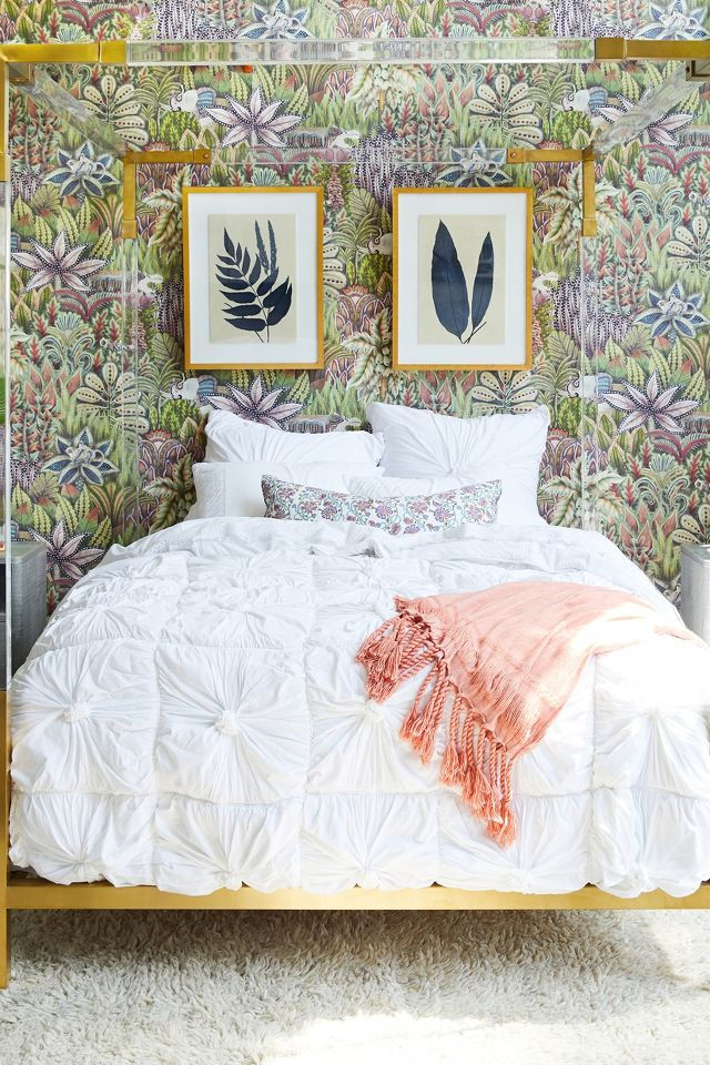 Whimsical blue, purple and green wallpaper in a bedroom with a modern acrylic bed and indigo fern wall art - Anthropologie. #bedroomdecor #indigoblue