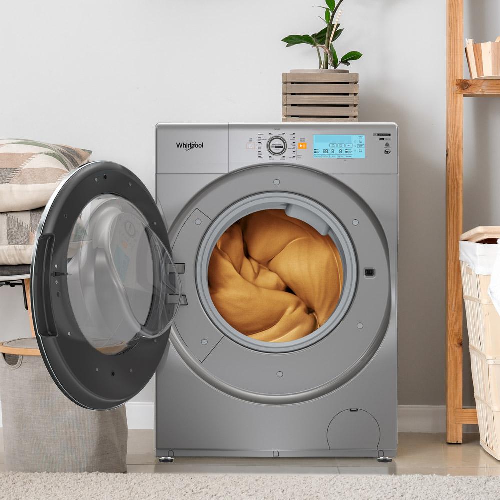 Lavasecadora Todo-En-Uno marca Whirlpool con 10 Kg de capacidad de lavado y 6Kg de secado. Ambientada en cuarto de ropas con apertura de tapa fontal cargada con un Edredón de gran dimensión.