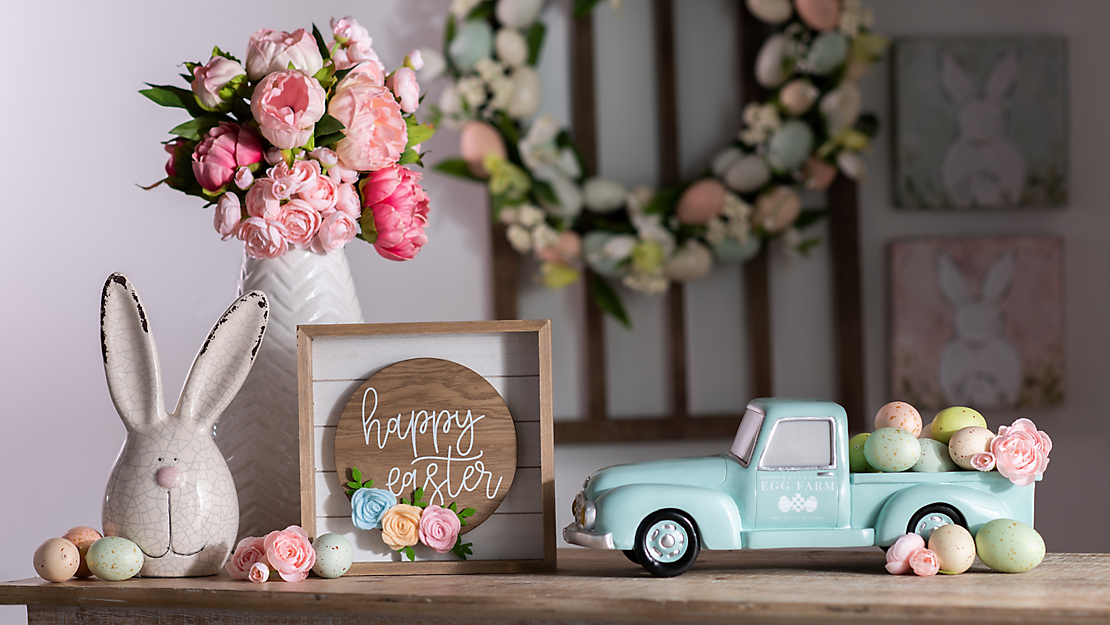 Easter decor including a floral arrangement, Happy Easter plaque, bunny head statue, and vintage inspired truck