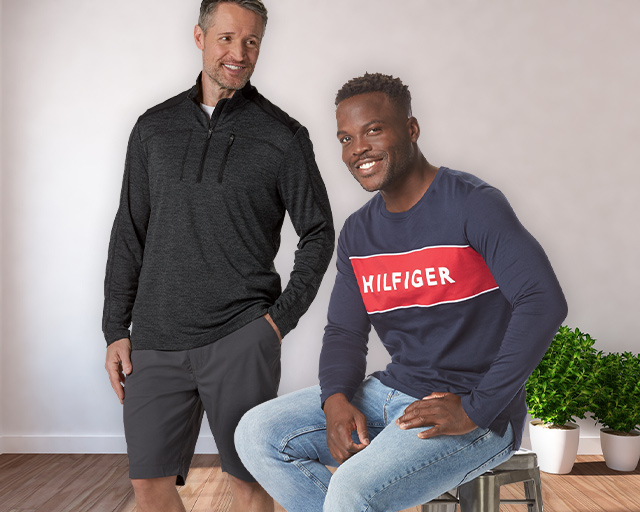 man wearing a half zip athletic jacket with a pair of shorts standing next to another man wearing a Tommy Hilfiger Long sleeve shirt and jeans