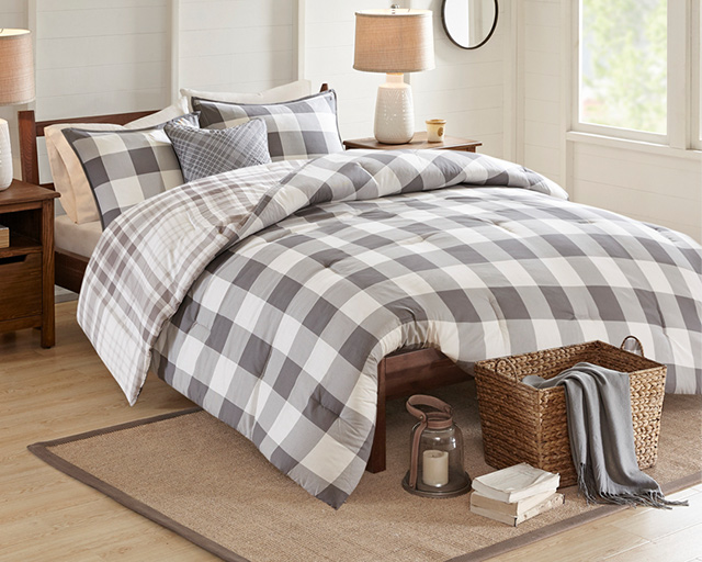 grey and white plaid bedding on a bed