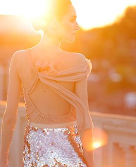 woman in sequin dress at sunset for holiday